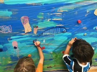 Niños pintando mural del mar
